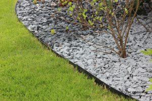 Pihan kauneusarvoihin liittyy pihan pintamateriaalit. Kuvassa nurmikon reuna, jossa on metallireunus. Se erottaa nurmikon kasvialueesta, jossa on kivi kate mullan pinnalla.