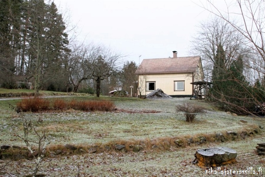 Vanhan pihan esittely ja sen historiaa. Kuvassa näkyy taustalla rintamamiestalon tyyppinen keltainen talo. Etualalla nurmikkoa ja matalia kivipengerryksiä.
