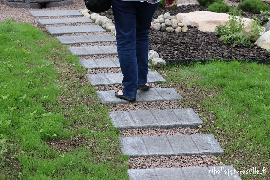 Askelkivet nurmikolla voivat olla kuten kuvassa suorakaiteen mallisia betonilaattoja. Kivien väleissä on pientä sepeliä.