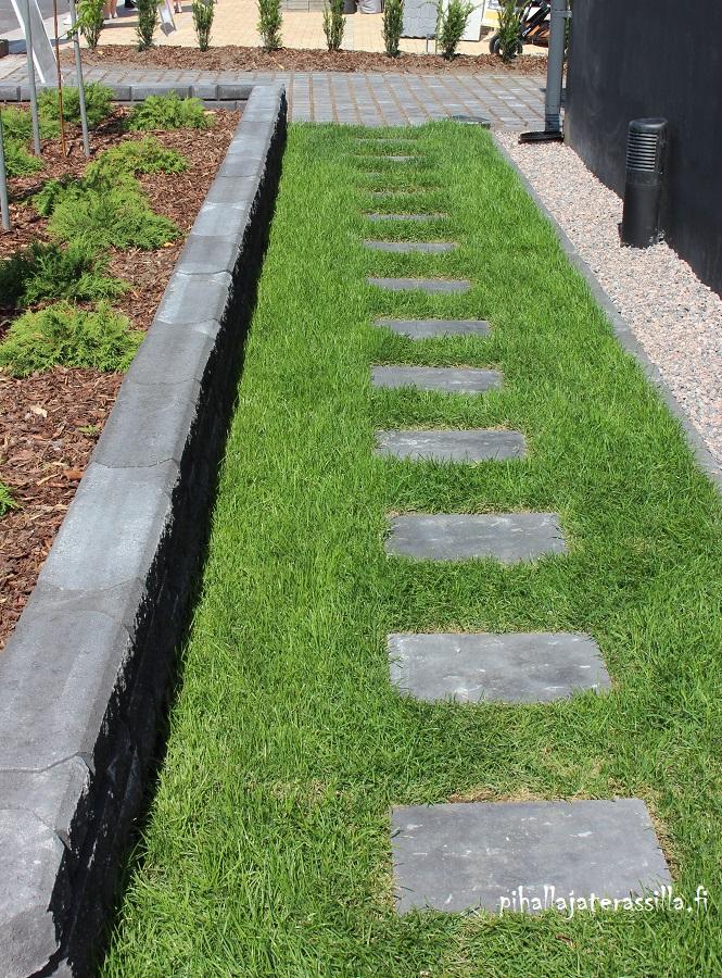 Askelkivet nurmikolla voivat olla kuten kuvassa harmaita neliön mallisia betonilaattoja. Askelkivipolun vieressä on matala betonimuurikiveys.