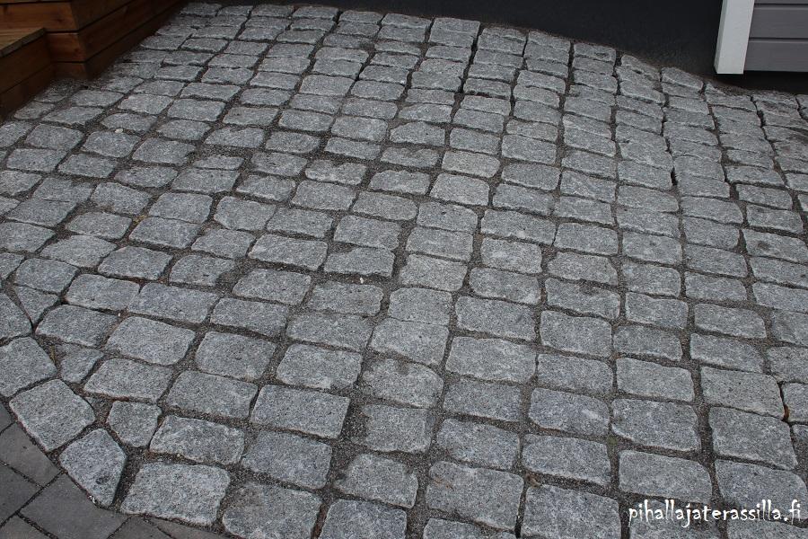 Kuvassa harmaata graniittinoppakiveä pihan pintana kaltevassa kohdassa.