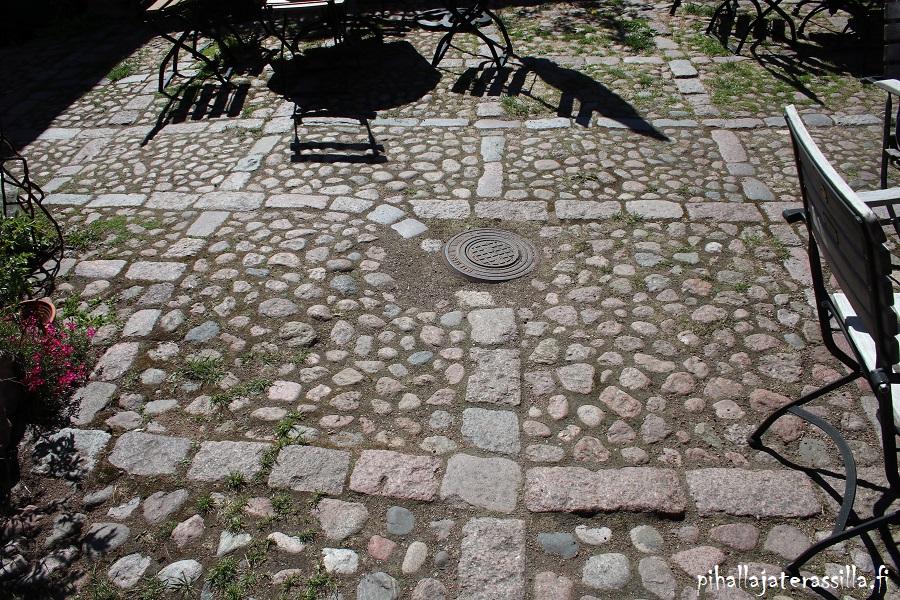 Kuvassa on luonnon pyöristämiä kiviä eli seulanpääkiveä eli mukulakiveä asennettuna pihan pintaan.