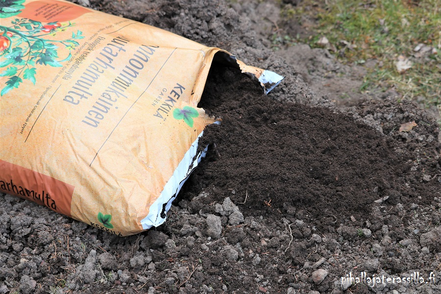 Viljelylaatikon mullan kunnostus. Kuvassa vanahan huonon mullan päällä Kekkilän Luonnonmukainen puutarhamulta säkki, josta otettu multaa ulos.